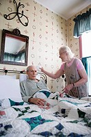 Senior woman affectionately tending to bedridden senior man
