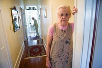 Elderly woman standing in hallway with feeble senior man in the background