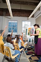 An art teacher standing by easel teaching her young students in art class
