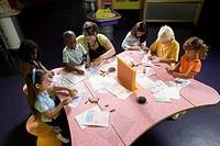 An art teacher teaching her young students in art class