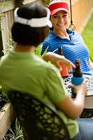 Two women sitting at table in backyard conversing