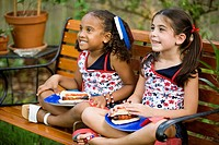 Girls sitting on bench with with a plate of hot dogs on their lap