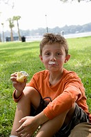 Boy eating a cupcake at a park