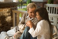 Mature interracial couple sitting on front porch