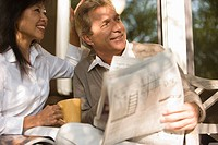 Mature inter_racial couple holding coffee mug and newspaper