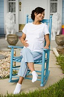 Pregnant woman sitting on a rocking chair in front of house