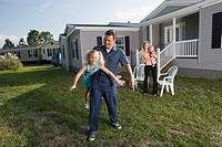 Portrait of a man playing with his blue_collar family in front of a trailer home