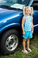 Portrait of a smiling girl standing by a car