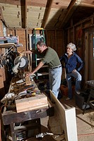 Mature man working with tools while wife watches