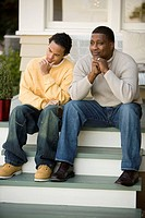 Father sitting with teenage son on front steps of house