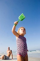 Young girl at the beach with father watching in background