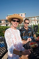 Portrait of mature couple in tropical outfits sitting at a table with hotel in the background