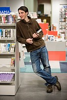 Teenage boy leaning on bookshelf in the library