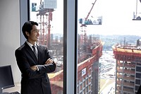 ´Business man with arms crossed looking out of office window, waist up´