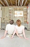 Couple sitting on floor in house under construction, rear view