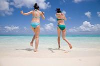 Two young women in bikini running on beach towards ocean, rear view
