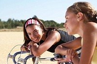Two girls 12-14 on bicycles, leaning, one looking at camera differential focus