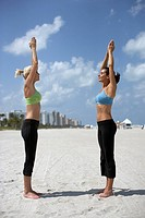 Two women doing yoga on beach, side view