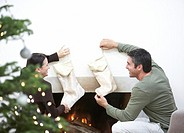 Mature couple hanging stockings over the fire place, rear view