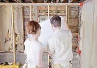Couple at construction site holding and looking at blueprints, rear view