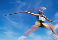 Man throwing javelin at track and field competition, blurred motion