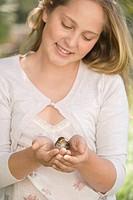 Smiling preteen girl holding bird in hands
