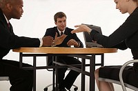 Businesspeople gesturing and conversing during meeting