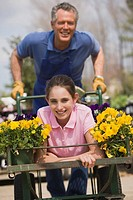 Man pushing teenage girl in flower cart