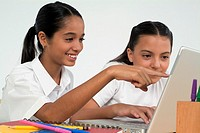 Two girls using laptop computer, with one pointing at computer screen, close-up