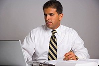 Businessman sitting in desk with laptop computer