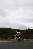 Cyclist riding on road, side view