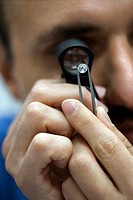 Gemologist inspecting diamond using loupe, close-up