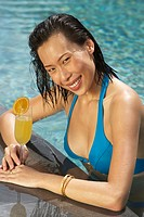 Young woman with orange juice in swimming pool, portrait