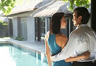 Young couple embracing by swimming pool, rear view