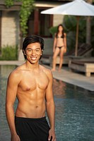Portrait of shirtless young man at swimming pool, out of focus woman in background