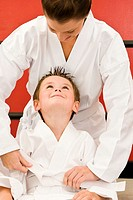 Karate teacher helping boy 4-5 years tie gi belt