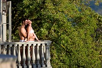 Young couple wearing underwear, embracing on balcony, side view
