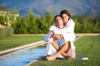 Young couple wearing white bath robes embracing outdoors by pool, smiling, portrait