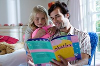 Father reading to daughter 6-8 from book, smiling