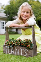 Girl 6-8 on grass leaning on handle of plant box, 'plants' written on box, smiling, portrait