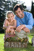 Father and daughter 6-8 crouching by plant box, leaning on handle, smiling, portrait