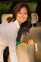 Smiling woman unloading groceries from car, portrait