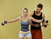 Woman lifting weights next to man holding clipboard, studio shot