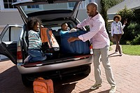 Son and daughter 6-10 helping father load luggage in back of car tilt