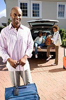 Man with suitcase in driveway, family by car in background, smiling, portrait (thumbnail)
