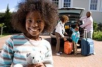Girl 8-10 holding toy in driveway, family by car in background, smiling, portrait