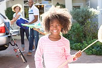 Girl 8-10 with fishing net in driveway, parents in background, smiling, portrait