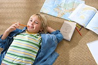 Boy 6-8 lying on floor by maps, pencil in mouth, smiling, portrait, elevated view