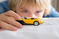 Boy 6-8 playing with toy car differential focus