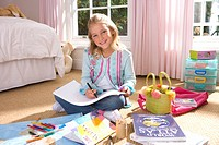 Girl 8-10 drawing in bedroom, smiling, portrait